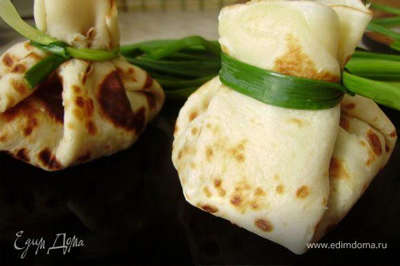 Теперь заворачиваем блинчики розочкой и перевязываем зеленым лучком... Причем в каждый блинчик вместе с начинкой кладем натертый сыр пармезан....На противень смазанный оливковым маслом и на 5 минут в духовой шкаф...