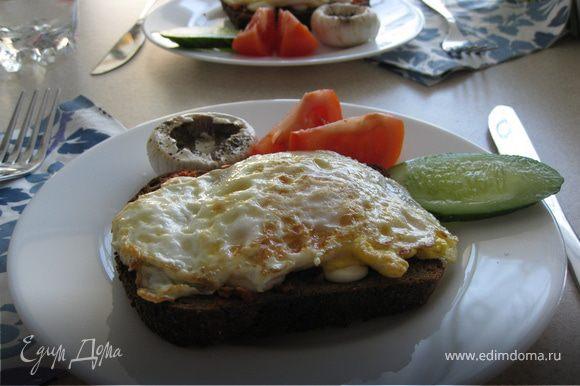 На сильно разогретой сковороде в небольшом количестве растительного масла обжарить яйцо с двух сторон так, чтоб желток в середине оставался жидким. Затем выложить на гренку. Добавить ломтик свежего огурчика, помидорки, добавить парочку оливок (забыла положить :) исправлюсь) и вуаля! Ваш завтрак готов!