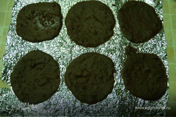 Растопить шоколад на водяной бане. Помять сильно фольгу и по две чайной ложке вылить на фольгу кружочки. Немного разровнять до толщины 2-3 мм. Отправить в холодильник.