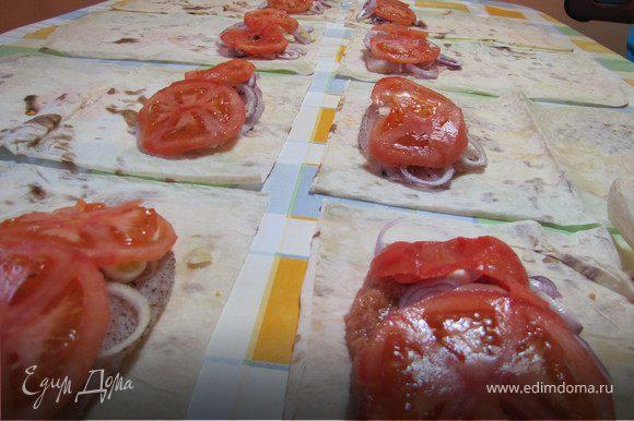 Выложить на лаваш по куску рыбного филе, посыпать колечками лука, добавить 2 кружочка томата.