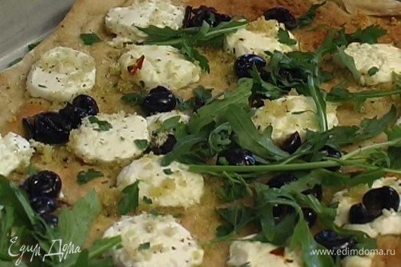 Готовую пиццу посыпать измельченными листьями базилика, руколой, сбрызнуть оставшимся оливковым маслом и лимонным соком.