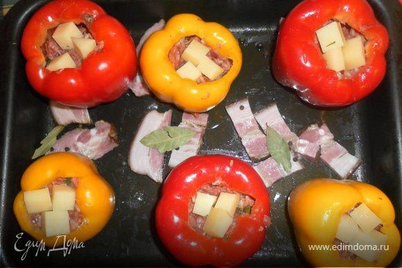"""1. У перчика срезаем верхушку, чистим от зёрен, хорошо промываем. Смазываем изнутри оливковым маслом и морской солью. 2. Варим рис до полуготовности, промываем холодной водой и даём ей полностью стечь. 3. ГОТОВИМ ФАРШ: обжариваем мелко нарезанную луковицу на оливковом масле до золотистого цвета, добавляем томатную пасту и с открытой крышкой пассируем на большом огне 2-3 минуты,постоянно помешивая. Хорошо перемешиваем фарш с получившейся массой и рисом. Добавляем мелко порубленную зелень, солим по вкусу, приправляем розмарином, тимьяном и паприкой (молотая приправка). 4. Начиняем перчики нашим фаршем, оставляя 1 см. до верхушки. Сверху на каждый кладём по 3 кубика сыра (он начнёт плавится и """"запечатает"""" наши перцы, чтобы фарш не выпал). 5. Выкладываем перцы на смазанный оливковым маслом противень. На дно противня выкладываем нарезанный шпик, лавровый лист и чёрный перец."""