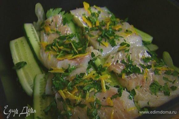 Рыбу нарезать порционными кусками, обвалять в смеси цедры с петрушкой, выложить в форму на огурцы, сбрызнуть оставшимся лимонным соком и оливковым маслом.