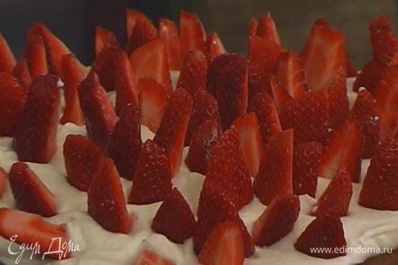 На каждый корж выложить слой взбитых сливок, затем слой клубники. Украсить последний слой взбитых сливок клубничными дольками, поставленными вертикально, и посыпать оставшейся сахарной пудрой.