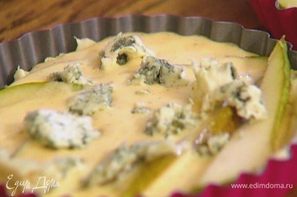 Яйцо слегка взбить со сметаной, солью и перцем, разлить в формочки с грушами, сверху выложить кусочки голубого сыра.