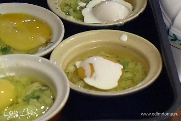 В небольшие формочки для выпекания выложить по 3 ст. ложки луковой смеси, влить по одному яйцу и по 1 ст. ложке сливок.