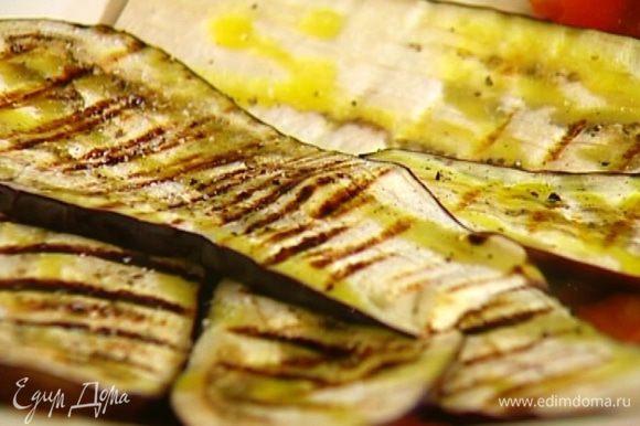 Выложить полоски перца на блюдо, сверху разложить баклажаны, сбрызнуть оливковым маслом, посолить, поперчить.