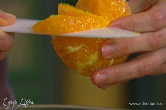 С апельсина срезать оставшуюся кожуру, захватив всю белую ее часть, удалить пленки и разрезать апельсин на сегменты так, чтобы сок капал на руколу.