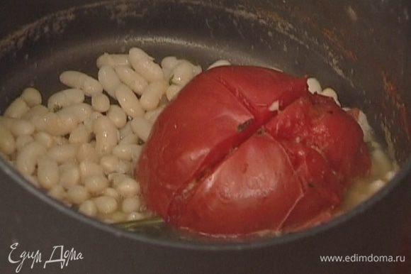 Вынуть из кастрюли с фасолью помидор, чеснок и петрушку.