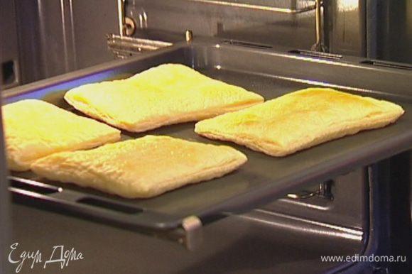 Поместить кусочки теста на противень, наколоть в нескольких местах вилкой и выпекать в разогретой духовке 10 минут, до полуготовности.
