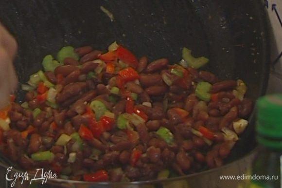 Отправить в сковороду к овощам отваренную фасоль, все перемешать и переложить в кастрюлю, в которой фасоль варилась.