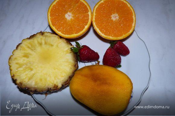 Выжать сок из апельсинов и ананаса. Манго и клубнику выложить в блендер, добавить сок апельсина и ананаса, взбить. Сахар по желанию.