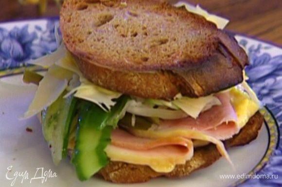 Хлеб смазать картофельно-яичной заправкой, положить на каждый кусок пару ломтиков ветчины, перец, черемшу, капусту, нарезанный огурец и сыр.