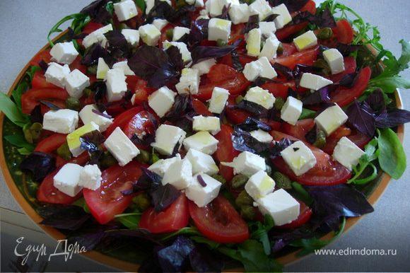 На блюдо выкладываем рукколу, затем помидоры, порезанные тонкими дольками, посыпаем их каперсами, добавляем фету кубиками. Сверху украшаем базиликом (можно чуть мелко нарезанного и целые листики),немного сбрызнуть оливковым маслом. Салат готов!