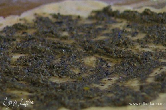 Раскатать тесто в пласт, смазать его тапенадом и накрыть помидоры смазанной стороной. Заправить края теста внутрь и отправить в духовку на 15−20 минут.