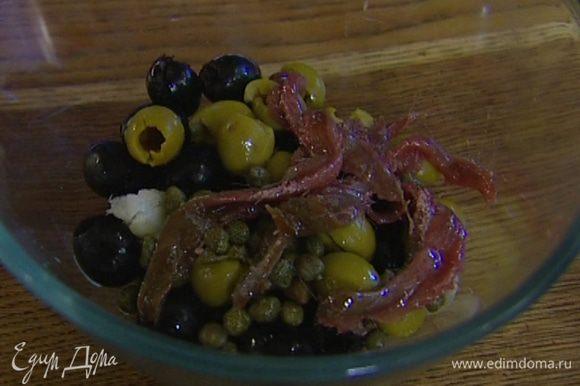 Приготовить тапенад: оливки соединить с каперсами, чесноком и анчоусами, добавить 1 ст. ложку оливкового масла, щепотку свежемолотого черного перца и взбить все до однородного состояния.