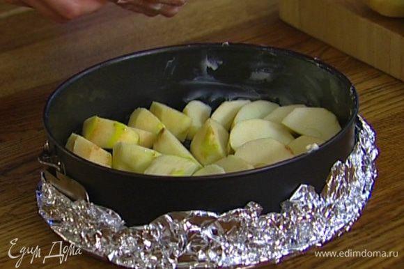 Смазать сливочным маслом разъемную форму (при необходимости выстелить фольгой, чтобы тесто не вытекало) и уложить в нее дольки яблок как можно плотнее друг к другу.