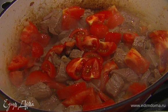 Помидоры крупно нарезать, отправить к мясу и томить все вместе 10‒15 минут на небольшом огне.