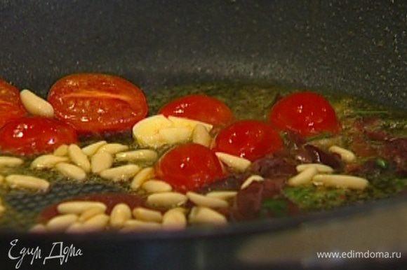 Выложить в сковороду к чесноку помидоры, оливки вместе с заправкой и кедровые орехи и обжаривать 1–2 минуты.