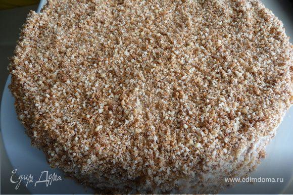 Готовим крошку для украшения: в блендере измельчить оставшиеся от коржей обрезки и грецкие орехи, получившейся крошкой обильно посыпать торт со всех сторон, обмазать боковинки. Сверху присыпать натертым замороженным шоколадом и убрать в холодильник пропитываться (минимум на 3 часа). Перед подачей можно еще посыпать тертым шоколадом.
