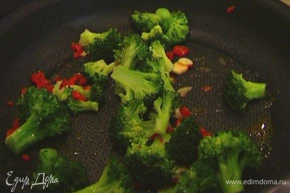 Разогреть в сковороде оставшееся оливковое масло, выложить брокколи, чеснок и чили. Посолить, поперчить, посыпать кунжутным семенем и перемешать. Обжаривать 2–3 минуты.