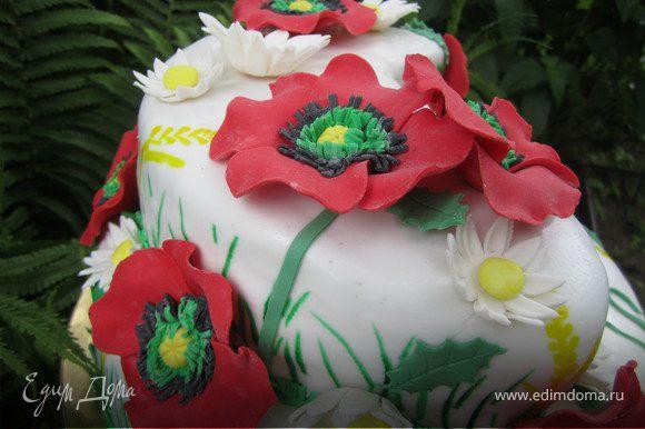 Зарание сделать цветы(маки - http://www.edimdoma.ru/recipes/24500 и ромашки - http://www.edimdoma.ru/recipes/22007). Из зеленой мастики вырезать листики. Украсить торт цветами и листиками. Цветы можно крепить на белый шоколад или разведенный желатин.