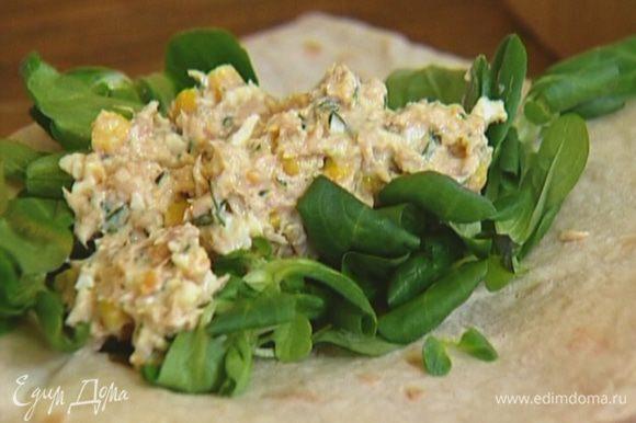 На край лаваша выложить листья салата, на них начинку из тунца.