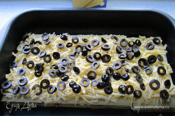 На предпоследний слой складываем половину тертого сыра и оливки, порезанные колечками.