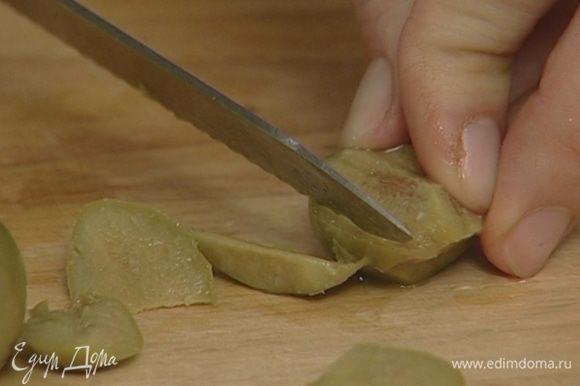 Оливки, удалив косточки, крупно нарезать.