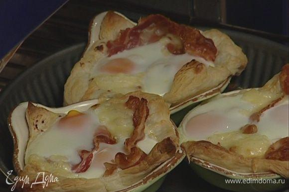 Вернуть формы в духовку и запекать яйца 12—15 минут.