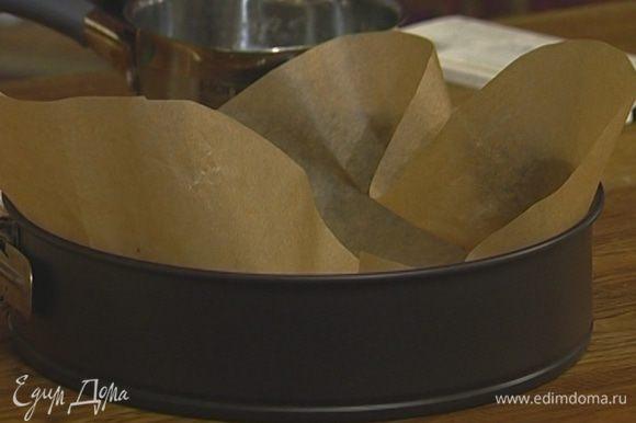Разъемную форму выстелить бумагой для выпечки, смазанной с обеих сторон сливочным маслом. Выложить тесто в форму, равномерно распределить тонким слоем и поставить на 5 минут в морозильную камеру.
