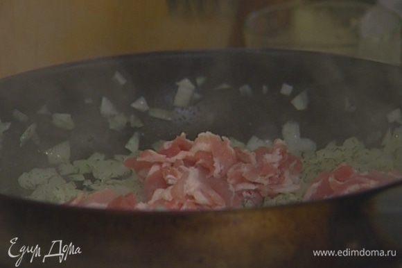 Разогреть в сковороде подсолнечное масло и обжарить лук вместе с беконом.