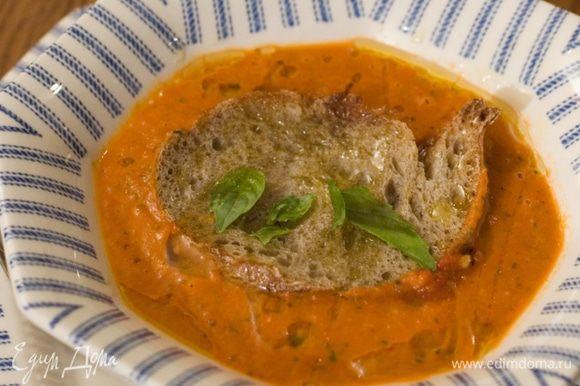 Налить взбитый суп в тарелку, сверху положить ложку измельченных, не взбитых помидоров, поджаристую гренку, сбрызнуть все оливковым маслом и подавать.