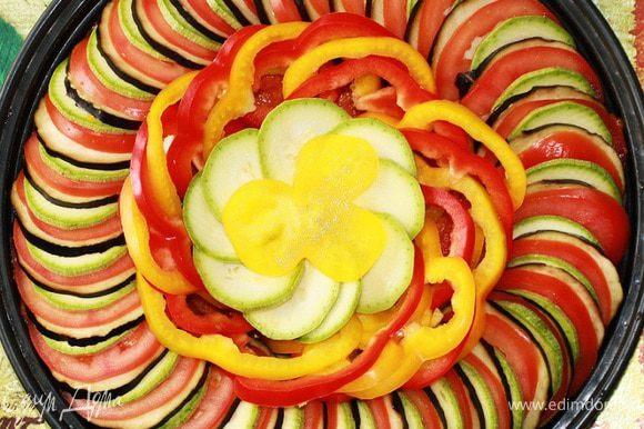 1 баклажан, 1 кабачок, 3 помидора нарезать тоненькими кружочками. Затем поверх соуса выложить ломтики овощей по кругу. Овощи чередовать повторяя последовательность, пока форма не будет плотно заполнена ими. Я укладываю овощи только в один круг, а затем украшаю середину болгарским перцем и кабачками. Сбрызнуть овощи оливковым маслом, посолить и поперчить. Листья с веточки тимьяна снять рукой и посыпать ими овощи.