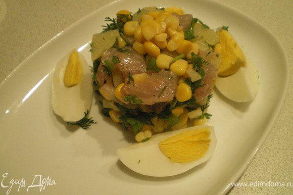 Рыбу отделить от костей, нарезать кубиками. Картофель также нарезать кубиками. Зелень измельчить. Добавить кукурузу. Посолить. Выложить салат, сбрызнуть оливковым маслом и украсить дольками яйца и горстью кукурузы.