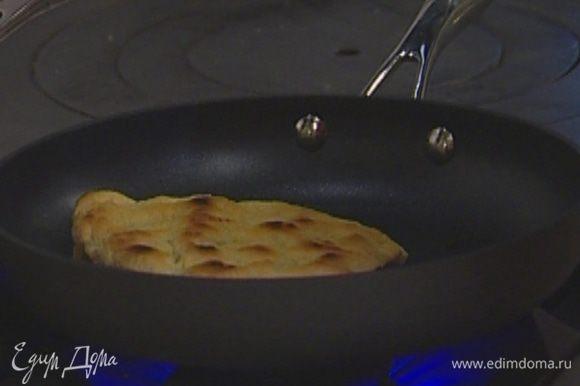 Уложить пышки на разогретую сковороду, накрыть крышкой и поджаривать по 2–3 минуты на каждой стороне.