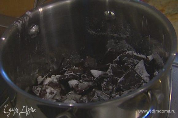 Шоколад растопить в маленькой кастрюле вместе с ромом и 80 г сахарной пудры, затем немного остудить.