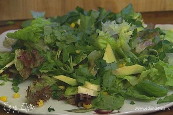 Присыпать листья салата сладкой кукурузой, петрушкой и базиликом, выложить сверху кусочки авокадо.