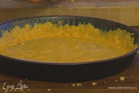 Форму для выпечки смазать оставшимся сливочным маслом. Тесто натереть на крупной терке прямо в форму и, прижимая пальцами, распределить его по всей поверхности, сделать бортики.