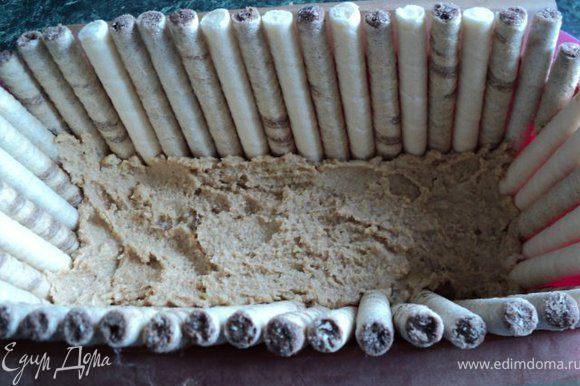 Прямоугольную форму размером 10х20см выстелить бумагой для запекания, чтобы края бумаги свешивались через бортики на 2см ( для облегчения вынимания торта из формы). На дно выложить смесь печения с маслом, бока торта выложить вафельными трубочками, прижимая их основой торта. Поставить в морозилку на несколько минут для застывания основы.