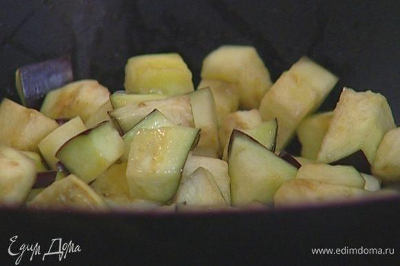 Разогреть в сковороде-вок растительное масло и обжаривать баклажаны 10–15 минут, постоянно помешивая.
