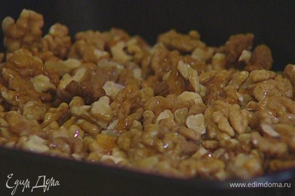 Орехи высыпать на противень, сбрызнуть ореховым маслом и подсушивать в духовке 2–3 минуты.