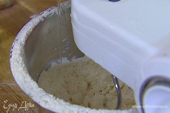 Когда масса приобретет консистенцию мелкой крошки, добавить 1 яйцо, желток и 80 мл ледяной воды и снова вымешать.