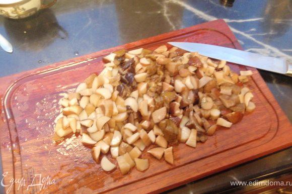 Отваренные грибы довольно мелко режем. И отправляем сначала на сухую сковороду, когда лишняя влага уйдет, добавляем масло и половину нашинкованного лука. Обжариваем до золотистости.