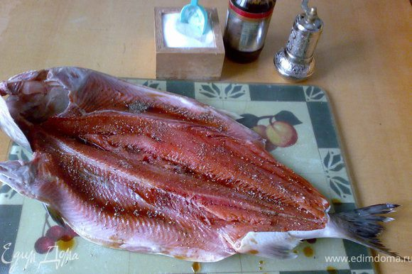 Разрезать горбушу вдоль хребта не разрезая шкурку. Посолить, поперчить и сбрызнуть рыбным соусом.