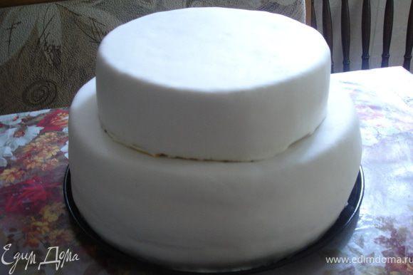 Раскатать мастику на столе, присыпанном сахарной пудрой, толщиной 5 мм и осторожно покрыть ей торты поочередно, следя за тем, чтобы были прикрыты боковые поверхности. Хорошо сформировать углы, аккуратно разглаживая излишки. Приглаживать ладонями или утюжком поверхность торта до тех пор, пока мастика хорошо не распределится по поверхности бисквита. Острым ножом или ножницами обрезать излишки мастики. Соединить этажи торта.