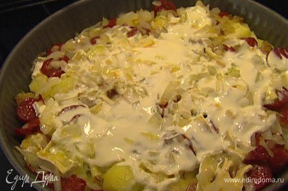 Колбаски, нарезанный кусочками сыр, обжаренные лук и чеснок выложить на картофель с салом, сверху смазать сметаной и отправить на 20 минут в разогретую духовку.