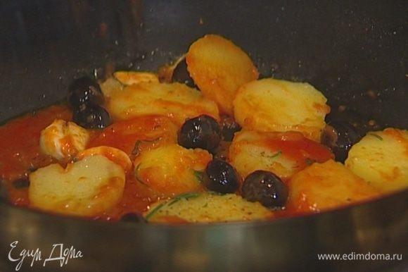 Разогреть в сковороде оставшееся оливковое масло, выложить нарезанный картофель, раздавленный чеснок, оливки и розмарин и обжаривать картофель до золотистого цвета, затем слегка посолить и поперчить, добавить протертые помидоры. Подавать рыбу с картофелем и оливками.