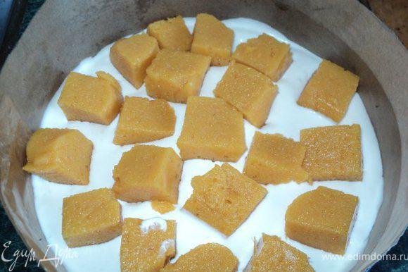 На корж вылить половину крема, выложить порезанное кубиками персиковое суфле,