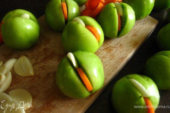 Морковь режем колечками,чеснок разрезаем каждую дольку вдоль на 4 части. Помидоры разрезаем пополам на 2/3 и в разрез вставляем кружок моркови и кусочек чеснока. Укладываем плотно в банку.